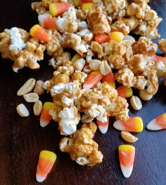 close up of peanut butter popcorn with candy corn and peanuts